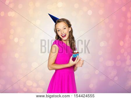 people, holidays and celebration concept - happy young woman or teen girl in pink dress and party cap with birthday cupcake over rose quartz and serenity lights background