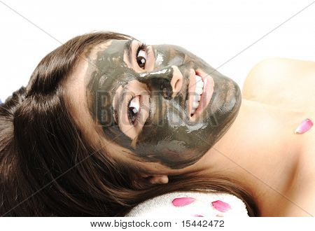 Sea Mud Mask on the woman's face.Spa. Young attractive woman laying on towel and smiling - white healthy teeth