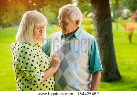 Sad elderly couple outdoor. Man next to a woman. What are you worried about. Truth is bitter.