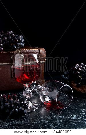 Glass Of Red Wine On Dark Marble Background. Cluster Of Blue Grapes On On Back Background.