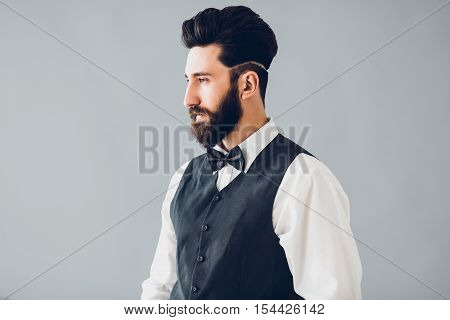 Young handsome bearded caucasian man posing indoors. Perfect skin and hairstyle. Wearing vest, white shirt, jeans. Studio portrait with dramatic light