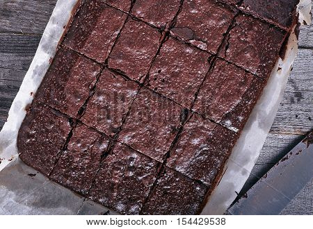 Homemade chocolate brownies cuted by squares on dark wood background woth baking sheet and pan. Top view.