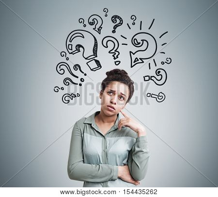 Portrait of African American woman standing near gray wall with multiple question marks drawn on it. Concept of question.