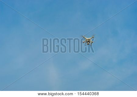 White Drone Hovering In A Bright Blue Sky And Clouds