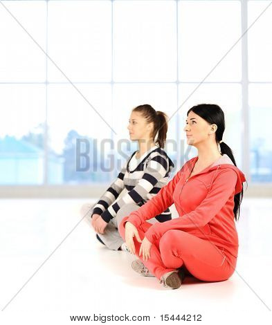 Two girls doing yoga and fitness bautiful bright surround