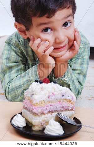 Very cute kid about to eat colorful cake