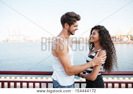 Happy multiethnic young couple standing and looking at each other in harbour
