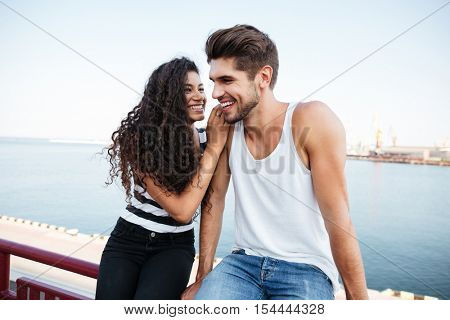 Cheerful multiethnic young couple sitting and laughing together in harbour