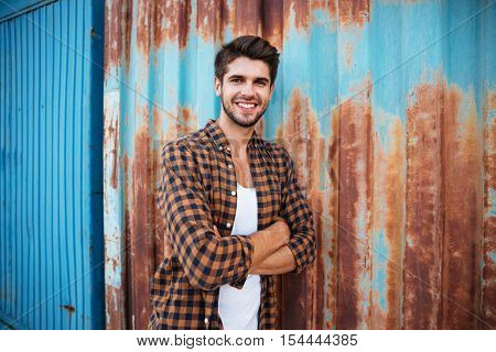 Portrait of smiling young man in checkered shirt standing with hands folded over blue metal background with rust