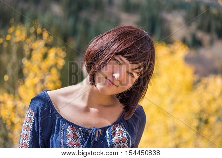 Portrait of young happy smiling woman with purple plum hair by autumn aspen trees with head tilted