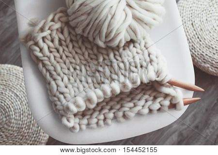 Thick yarn and wooden needles on modern plastic chair in living room, top view. Chunky knit.