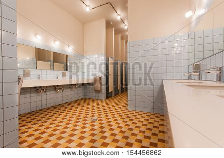 Empty restroom with washbasin and seperated toilet cabins in a modern youth hostel