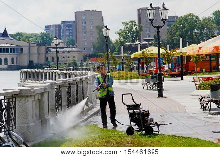 Kaliningrad Russia - August 3 2016: The worker is cleaning fence with high pressure water cleaner