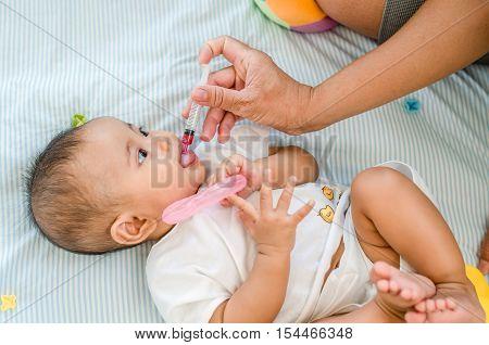 Asian baby girl feeding with liquid medicine