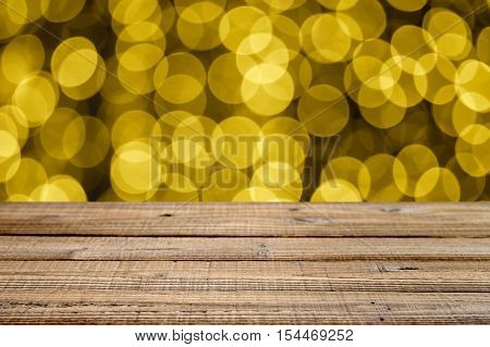 Old wooden table with golden festive bokeh. Shallow depth of field