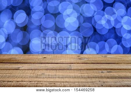Old wooden table with blue festive bokeh. Shallow depth of field
