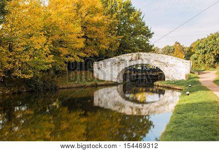 British autumn landscape. Old brick bridge over the canal.