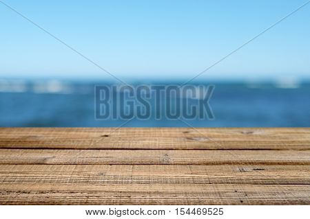 Wooden table with blue sea and sky background. Shallow depth of field