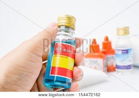 Hand holding ethyl alcohol with betadine gauze dressing and bandages on white background