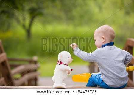 Cute little toddler boy sitting on wooden bridge and playing with white teddy bear in the park on sunny day. Happy child playing with toy. Children playing outdoors. Lifestyle and childhood concept