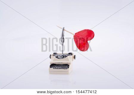 Heart shape icon on a typewriter on white background