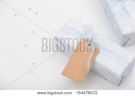 Top view on nicely wrapped gifts in the paper with stars and light blue ribbon and mock-up tag on the white background. Presents for birthday Christmas or any celebration. Holidays concept.