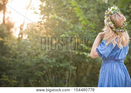 Back view on beautiful young woman in wild flowers wreath watching sunset in the park.