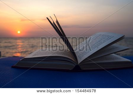 Book on the beach of blue sea. Back to school. Seaview.