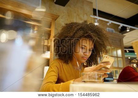 Girl in coffee shop websurfing with smartphone