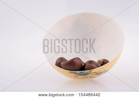 Fresh chestnuts in a bowl on a white background