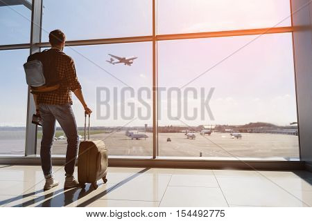 Calm male tourist is standing in airport and looking at aircraft flight through window. He is holding tickets and suitcase. Sunset