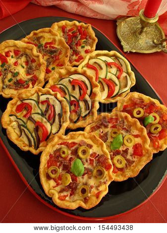 Colorful mini pies with vegetables, prosciutto, anchovies, olives, on black plate