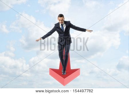 A businessman full-faced walking straight balancing on a giant red arrow on the background of a blue sky. Way to success. Business and management. Reaching aims.