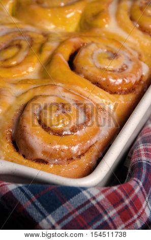 bun of pumpkin with cinnamon in the form of snails in a creamy glaze ceramic roasting pan