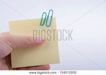 Hand Holding A Note Paper With Paper Clips