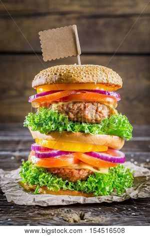 Tasty and big double-decker burger on old wooden table