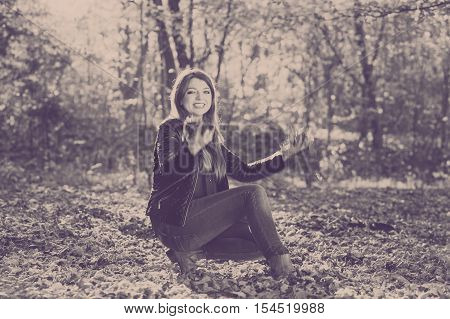 Nature outdoor playing relax leisure concept. Crazy girl throwing leaves. Euphoric woman tossing around autumnal foliage having time of her life.