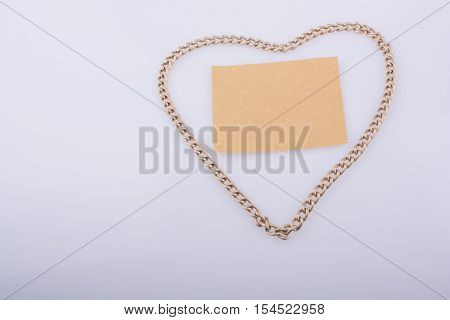 Chain forms a heart shape with a brown blank paper in it