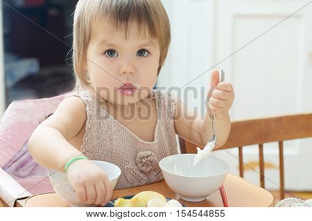 little girl eating in baby sitting little child eating sour cream with fruits in the home kitchen