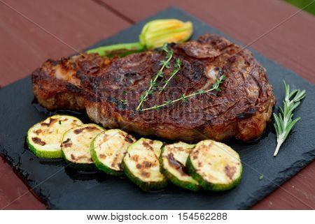 Rib eye steak with vegetables on a slate plate