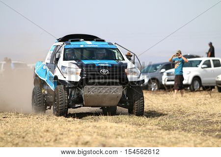 Speeding White And Blue Toyota Hilux Twin Cab Rally Car Front View