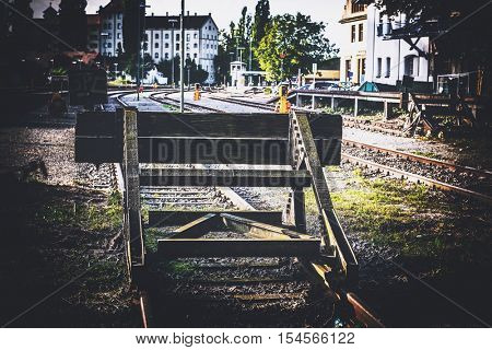 Steel buffer blocking a disused railway siding marking the end of the track in a city with a side vignette