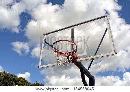 basketball backboard on blue cloudy sky background in park