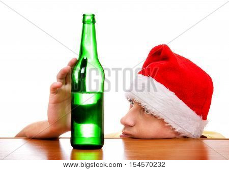 Sad Young Man in Santa's Hat with the Beer at the Table on the White Background