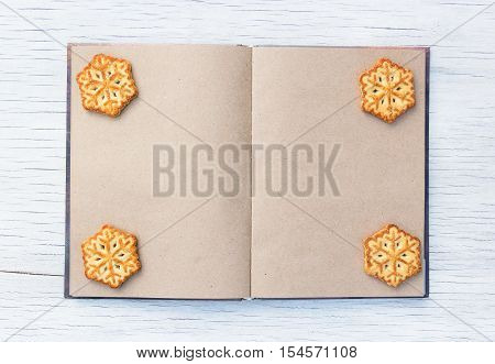 Notepad with blank pages and Christmas cookies in the shape of snowflakes. A book with blank pages and a New Year's cookies. Culinary book on white wooden table. Copy space.