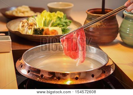 Raw beef getting down boiling in hot pot shabu
