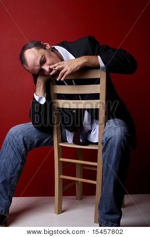 middleage gentleman sitting in a chair and thinking