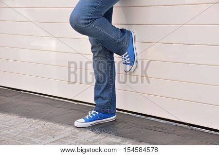 young woman with jeans and sneakers standing on one leg and leaning against a white metal door of a garage