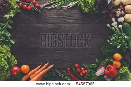 Frame of fresh organic vegetables on rustic wood background. Healthy natural food with copy space. Tomato, lettuce, carrot, garlic, pepper and other cooking ingredients top view, filtered
