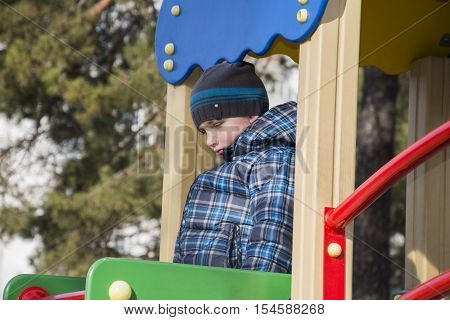 In the spring of the playground is a sad hurt little boy.